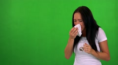 Young pretty woman blow one's nose - green screen - studio  Stock Footage