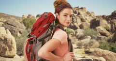 Young woman in her 20s hiking through Joshua Tree. Portrait of woman smiling Stock Footage