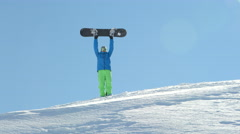 Cheerful snowboarder standing on mountaintop, raising a snowboard over his head Stock Footage