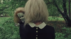 Stylized shot creepy white faced woman with a doll in the grass in the woods Stock Footage
