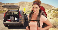 Happy young woman in her 20s backpacker ready for her hike in the desert. Joshua Stock Footage