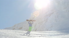 Extreme freeride snowboarder reaching the mountaintop and raising his snowboard Stock Footage