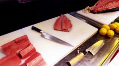 Tuna fish filet in sushi restaurant kitchen 4k video. Chef take bluefin, knife Stock Footage