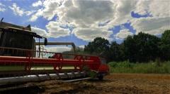 Thresher combine harvester cutter bars unloading grain. Farm vehicle 4k video Stock Footage