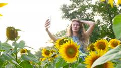 Attractive girl model does selfie near sunflowers. HD Stock Footage