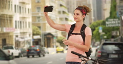 Millennial using smartphone to take self portraits while biking through the Stock Footage