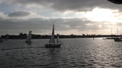 A sailboat passes the late afternoon sun cast behind a cloudy sky.mp4 Stock Footage