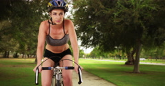 Woman in her 20s riding her bike through the park. Front view of healthy fit Stock Footage