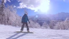 Snowboarder girl snowboarding down the ski slope in sunny mountain ski resort Stock Footage