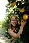Pretty islam woman in orange grove smiling, real muslim girl cheerful Stock Photos
