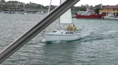 Tracking shot of sailboat attacking anchored Race Committee motorboat with wa Stock Footage