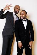 Two afro-american businessmen in black suits emotional posing, gesturing Stock Photos