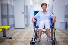 Sad senior patient sitting on a wheelchair in hospital Stock Photos