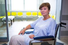 Portrait of sad senior patient sitting on a wheelchair in hospital Stock Photos