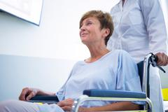 Doctor pushing senior patient on wheelchair in hospital Stock Photos
