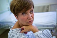 Portrait of sad senior patient sitting on a bed in hospital room Stock Photos