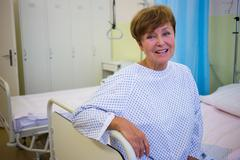 Portrait of smiling senior patient sitting on a bed in hospital room Stock Photos