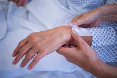 Nurse attaching iv drip on patient s hand in hospital Stock Photos