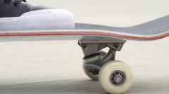 SLOW MOTION DOF: Skater skateboarding standing on deck, skate wheels spinning Stock Footage