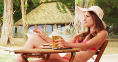 Attractive woman sitting at the beach enjoying food and drink. Young woman in Stock Footage