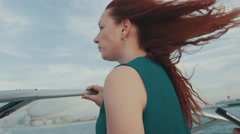 Red hair young girl in turquoise dress drive motor boat. Summer evening. Wind Stock Footage