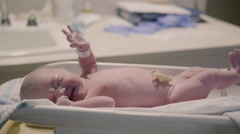 Naked Newborn Baby on Hospital Scale with Umbilical Cord Clamped Stock Footage