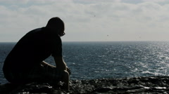 Depressed guy thinks about suicide in front of the sea Stock Footage
