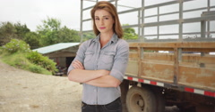 Young woman standing by farm truck. Woman in her 20s carrying on her family Stock Footage