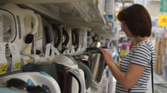 Woman looking at kettles in the appliance shop Stock Footage