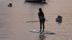 Stand up paddle boarder floating into amazing golden sunset in harbor.mp4 Stock Footage
