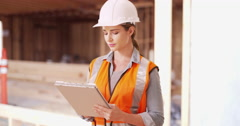 Woman construction manager writing notes down on her clipboard. Confident Stock Footage