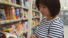 Woman looking through cookery book in the shop Stock Footage