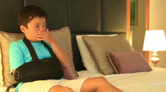 Child  with injured arm and bandage  watching tv on the bed Stock Footage