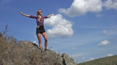 Young blonde woman tourist on the cliff  looking  on the landscape and stretc Stock Footage