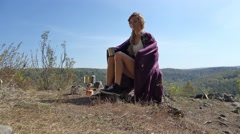 Young blonde woman tourist wrapped in a vinous blanket sitting on camping cha Stock Footage