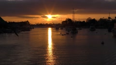 Peaceful golden sunset in harbor as seen from motor boat moving through moori Stock Footage