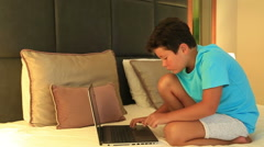 Child doing homework with laptop on the bed Stock Footage