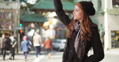 Attractive woman waving for a taxi cab to pick her up. Cute girl in her 20s Stock Footage