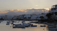 Arrecife, canarias- clouds rushing over a small harbor with moored boats Stock Footage