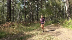 Young blonde woman tourist with a backpack goes along path in siberian forest Stock Footage