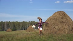 Blonde country girl running and jumping in the field among haystacks Stock Footage