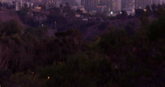 Tilt up from dark hills to Downtown Los Angeles skyline at dusk 4K Stock Footage