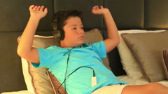 Child with headphone lying on a bed and listening to music with Mp3 player Stock Footage