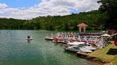View of Lake Pier with Row Boats against Green Hills Blue Sky Stock Footage