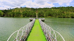 Narrow Lacy Bridge to Lighthouse in Lake Middle against Hill Stock Footage
