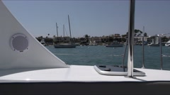 Sailing in harbor on catamaran looking from starboard aft area to moored boat Stock Footage