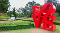 Red Word Love Sculpture at Flowerbed in Park in Vietnam Stock Footage