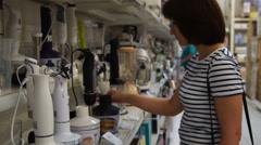 Woman choosing blender in the store Stock Footage