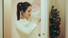 Young beautiful woman decorator hangs on the door a beautiful Christmas wreath Stock Footage