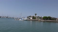 Mansion at end of island in harbor with small motor boat passing in the chann Stock Footage